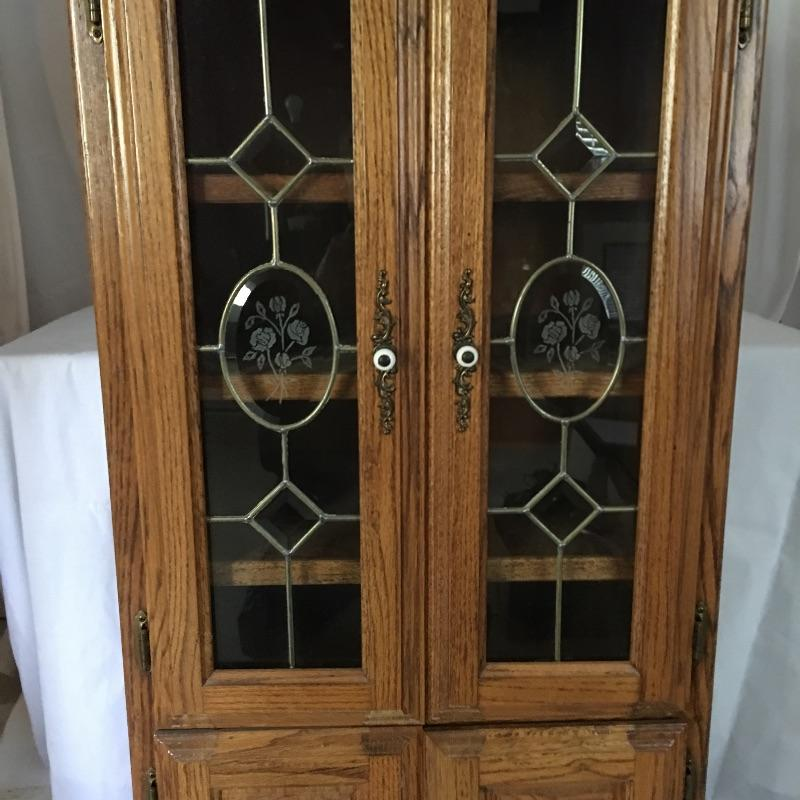 "Handsome wooden cabinet with glass inserts on top doors. Cabinet has four shelves with top shelf on slides. Will need to go down small flight of stairs to move out of home. Cabinet measures 16.75"" x 25.25"" x 50"".  Local Pickup Only"