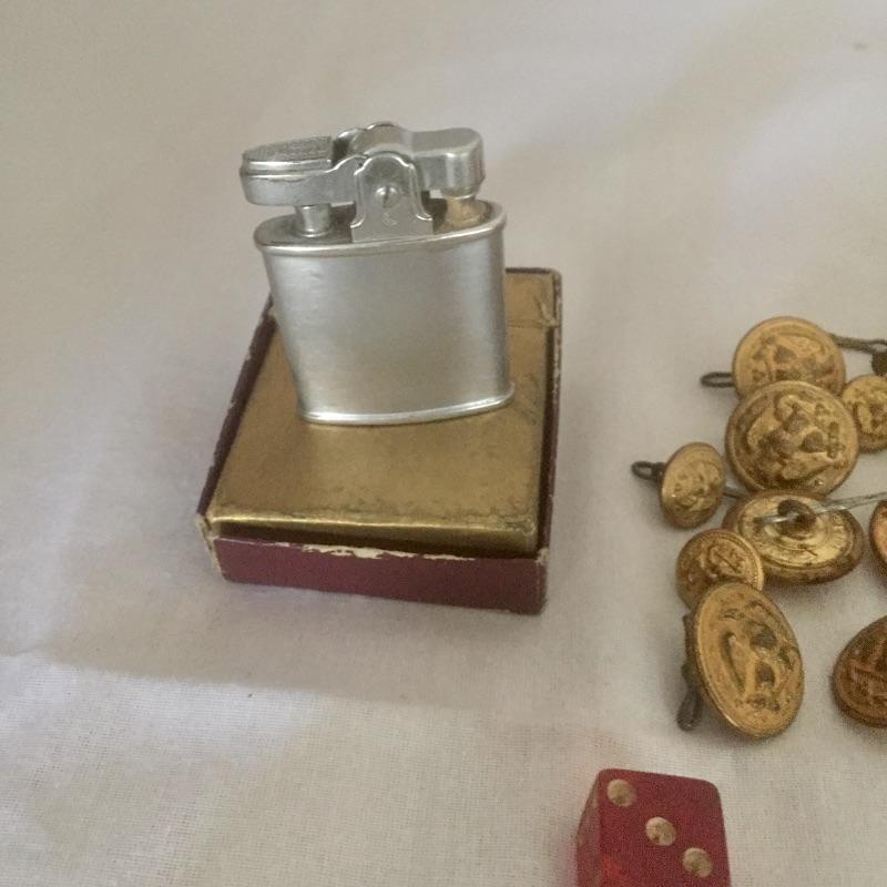 A unique collection of Badges, Pins, Uniform Buttons, Dog Tags, Bullet and engraved Zippo Lighter with original box and more, see images.  Pins are possibly WWll Vintage Army Air Force Brass Wings. Shipping Available.