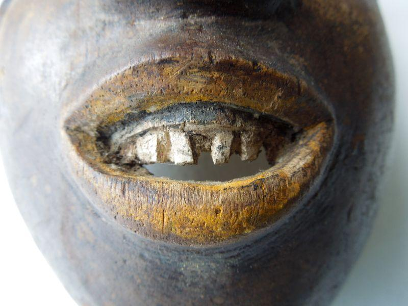 """Magnificently carved and aged mask with attached spotted animal resembling a hyena or oscelot. From the guro tribe of Ivory coast West Africa. Wood and pigments varying from shiny to powdery brown tobacco spit consistency. Teeth are carved wood. Damage to one ear of animal. The words """"Guro tribe"""" are written in pencil on inside of mask. 14"""" high x 6.5"""" wide."""