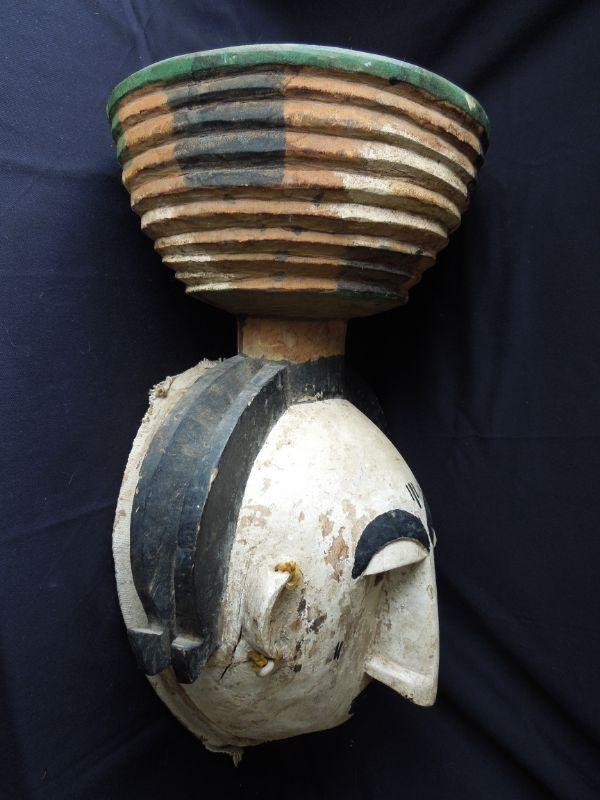 """This fascinating mask is likely made by the Igbo peoples of Afrikpo, Nigeria. 19th-20th century. Made of wood, pigment, cloth and cowrie shell earrings. There is a woven cloth band around the outer rim of the mask. An attached banded wood bowl sits on top of the mask. 20"""" high x 11.5"""" wide. Shows age."""