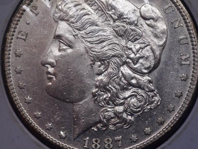 1887 S Morgan Silver Dollar in AU Condition Check out the Detail and the Beauty of this coin It has been secured in a coin holder to protect it  This Coin has a value of 125 to 1700   Inventory 86