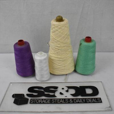 4 large spools of thread: White, Cream, purple, and green