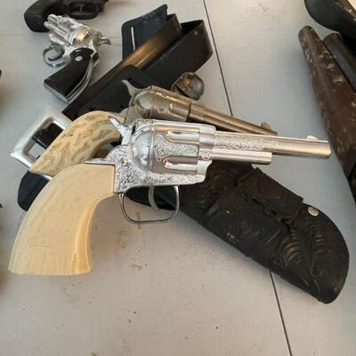Pair of vintage toy guns and belt