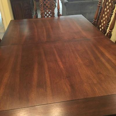 Solid ornate pecan wood dining table w/10 chairs and 3 leaves.