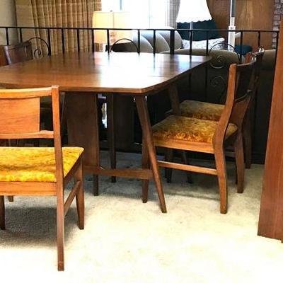 Mid Century Dining Table with 3 leaves and 8 Chairs. Wood on table and chairs is in very nice condition. The chairs could use new fabric...