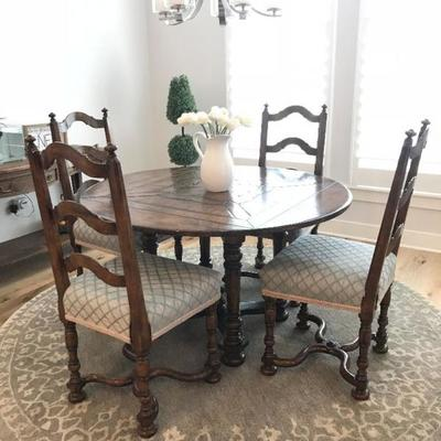 Custom made dining table and 4 chairs. Table is round with drop leaves to make it square. Originally purchased for $10,000. Estate sale...