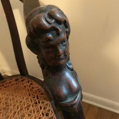 Closeup of the Woman bust carved into these wood chairs.