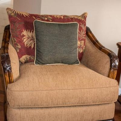 Two matching oversized upholstered chairs by Cindy Crawford with contrasting pillows, carved arms and rich wood accents.