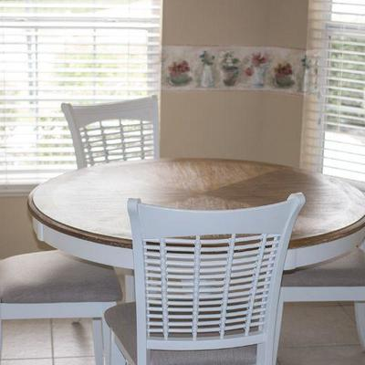 Kitchen dining set with driftwood-finish top and four white chairs with neutrally upholstered seat cushions.  Hillsdale 48