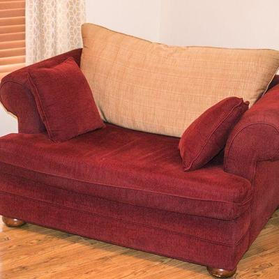 Overstuffed, double chair with contrasting pillows.