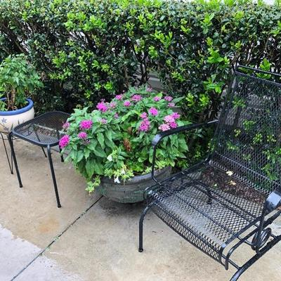 Wrought Iron Chair and side table. Large potted plants.