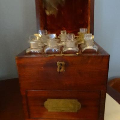 Apothecary traveling case . Drawers open up at the bottom to hold additional bottles, and supplies. a pin locks the case.