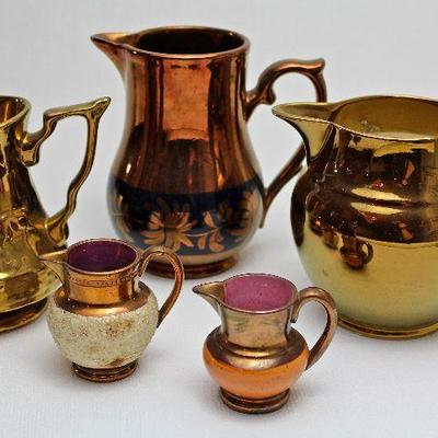 eclectic collection of pottery, including luster glazed pitchers