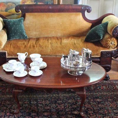 period Empire sofa, Oriental rug, English tea service, mahogany oval talbe