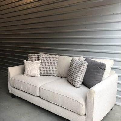 Beautiful grey fabric couch, comes with 6 decorative grey toned textured pillows and dark wood legs. The dimensions of the couch are 28...