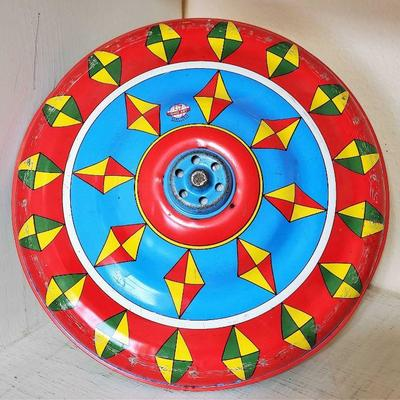 Bottom view of vintage tin spin top toy.