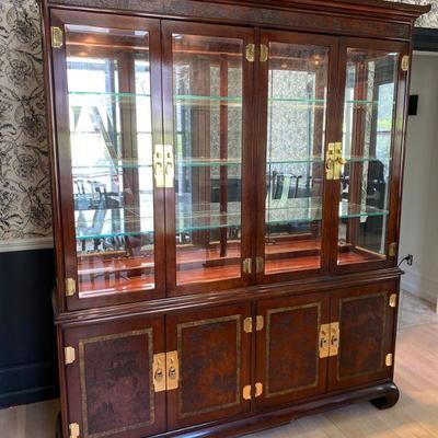 Drexel Heritage Ming Treasures collection china display cabinet with same carved design on lower doors. Interior lighting for glass...