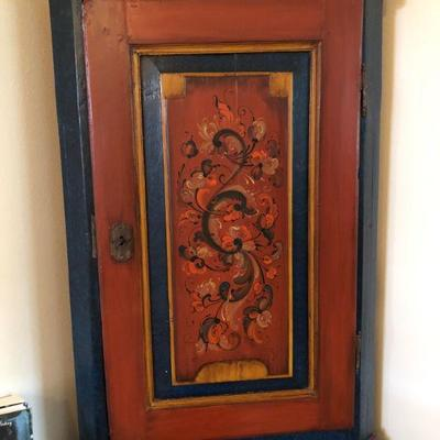 This is a mid 19th century hand crafted corner hanging cabinet that has been repainted. The interior of the door has a hand painted scene...