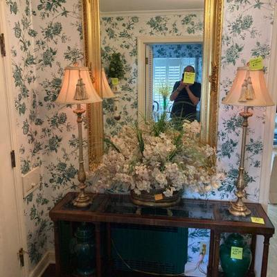 outstanding mirror, glass top console table stately lamps and a pair of decorative ginger jars.