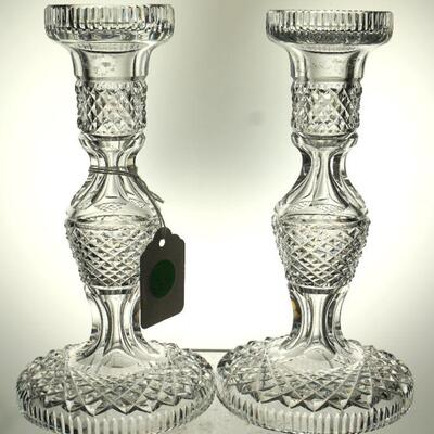 A pair of Hand Cut Waterford Crystal single candlesticks, decorated in paneled diamond pattern, marked at the undersides. Measuring H. 7...