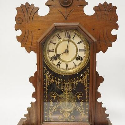 1090CARVED WALNUT GINGERBREAD CLOCK, HAS PAINTED DOOR & A FRAGMENT OF THE ORIGINAL LABEL ON THE BACK. 14 1/2 IN W 21 1/2 IN H 100200...