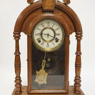 1089CARVED WALNUT GINGERBREAD CLOCK, HAS FULL TURNED COLUMNS & AN OLD STORE LABEL BARGAIN BARN NEPTUNE. 14 5/8 IN W 22 1/2 IN H 100200...
