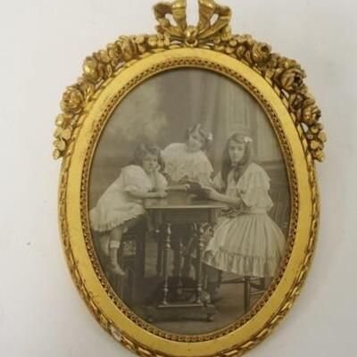 1008	ANTIQUE GILT OVAL FRAME W/PHOTO OF 3 YOUNG GIRLS, 7 1/2 IN X 5 1/2 IN