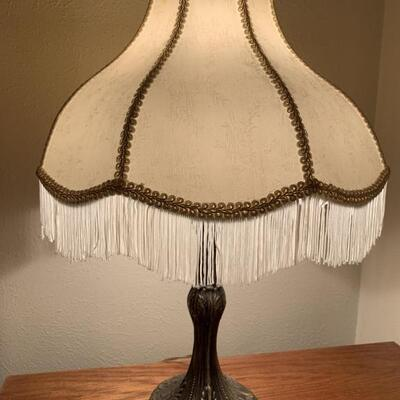 Replica of a Vintage Lamp. Appears to have aluminum base and cloth fringe lampshade. It works and is 21 inches tall.