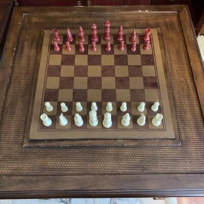 A wooden gaming table complete with chess/checkers board and reverse side for backgammon. There is a complete chess set and complete...