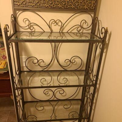 Pretty metal bakers rack with four glass shelves. Leaf and vine design flows across the top piece. The shelf is painted metallic grey and...