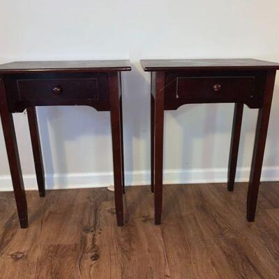 A matching set of wood end tables with single pull out draw with wood knob accents. The surfaces show signs of wear on both tables....