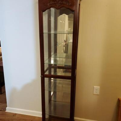Slim lighted curio cabinet in a cherry finish. Cabinet has 4 glass shelves. Could not get light to work, may just need a new bulb....