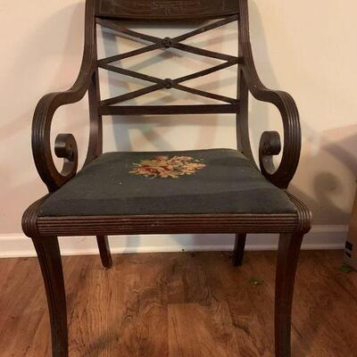 This is an Antique looking wooden chair with decorative scroll woodwork and artistic flourishes throughout, there is a floral design done...