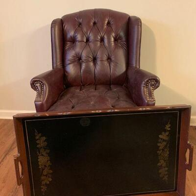 This Queen Anne chair comes with wooden serving tray and features oxblood fabric and has brass stud accents. The serving tray has a...