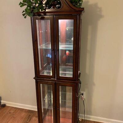 This is a Cherry and glass curio cabinet by Amelia. It has a top light with rolled toggle switch that is in working order. There is one...
