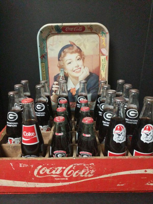 """A combination of two great things, Coke and Georgia!! 13 full bottles of the 1980 National Champions, 2 full bottles of the 1985 Bicentennial, 1 full bottle of James Edward Oglethorpe 250th Birthday, 6 full bottles of 2002 Conference Champions. Comes with Coca Cola wooden carrier (18.5""""x12""""x4.5"""")and a decorative tin tray (10.5""""x13""""x1.5"""")  https://ctbids.com/#!/description/share/768458"""