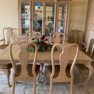 Dining table with 2 arm chairs, 6 chairs & 2 leaves. Hutch with Wedgwood