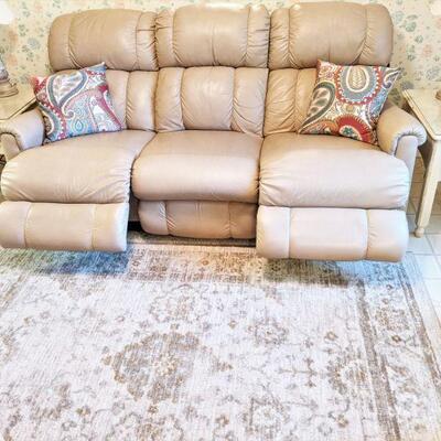 Dual reclining beige leather lazy boy sofa. Tag still attached