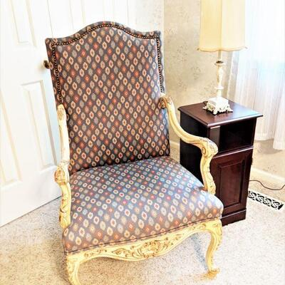 Upholstered armchair with carved legs