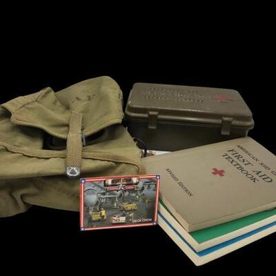 This lot contains military memorabilia like books, first aid kit, USAF bag, and a Desert Storm trading card....